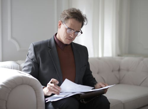 Elegant adult man in jacket and glasses looking through documents while sitting on white sofa in luxury room